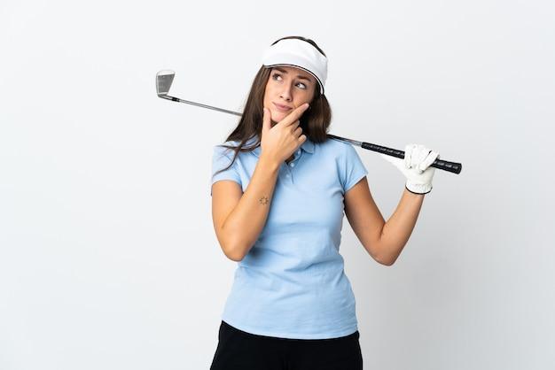 Mulher jovem golfista sobre fundo branco isolado tendo dúvidas