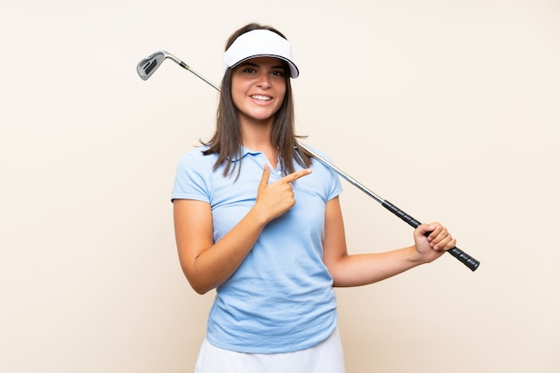 Mulher jovem golfista sobre parede isolada, apontando para o lado para apresentar um produto