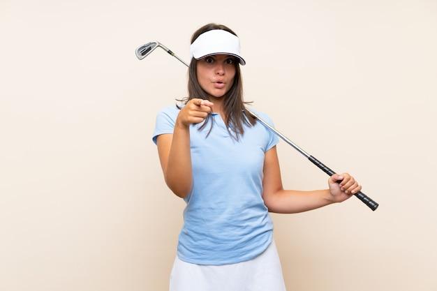 Mulher jovem golfista sobre parede isolada surpreso e apontando a frente
