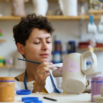 Mulher jovem gosta de pintar um jarro de barro com tinta depois de moldar e esculpir o jarro de cerâmica