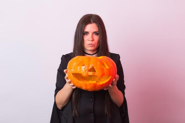 Mulher jovem gótica com fantasia de halloween bruxa com uma abóbora esculpida.