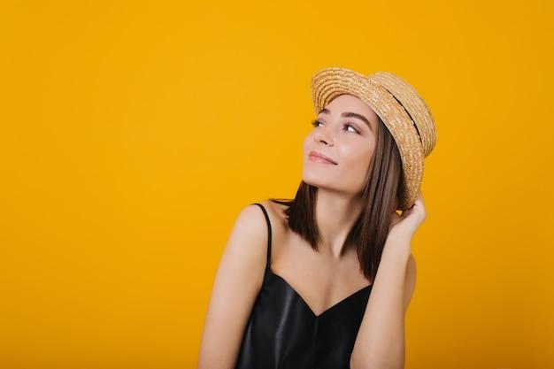 Mulher jovem graciosa no top de seda desfrutando. retrato de uma linda garota tocando seu chapéu de palha.