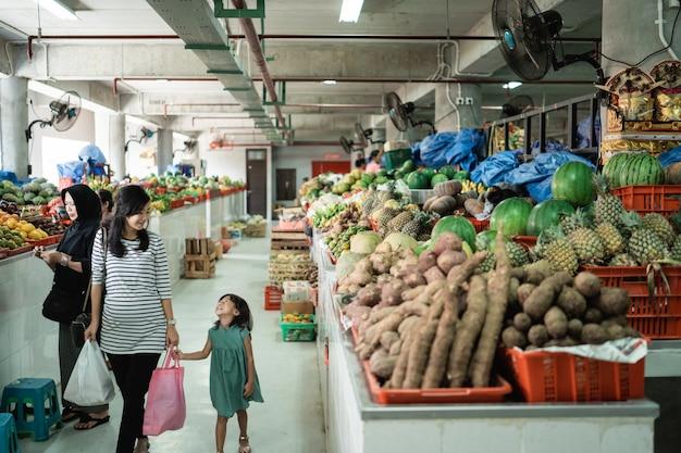 Mulher jovem grávida andar com sua filha carregando saco plástico