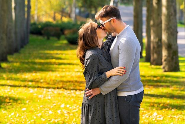 Mulher jovem grávida beijando o marido enquanto eles se abraçam ao ar livre em um parque arborizado de outono