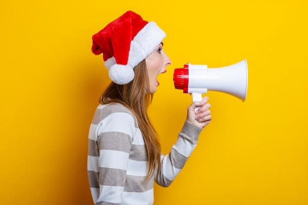 Mulher jovem grita em um megafone em um fundo amarelo.