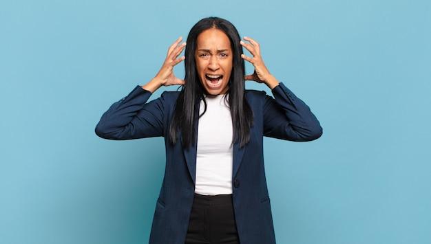 Mulher jovem gritando com as mãos para o alto, sentindo-se furiosa, frustrada, estressada e chateada