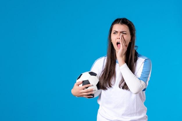 Mulher jovem gritando de frente segurando uma bola de futebol no azul