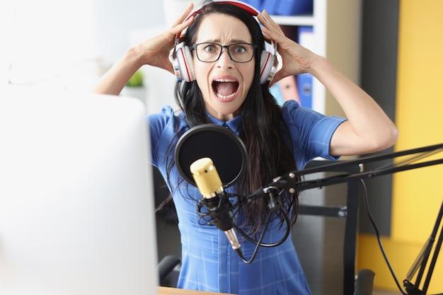 Mulher jovem gritando em fones de ouvido na frente do microfone conceito de más notícias