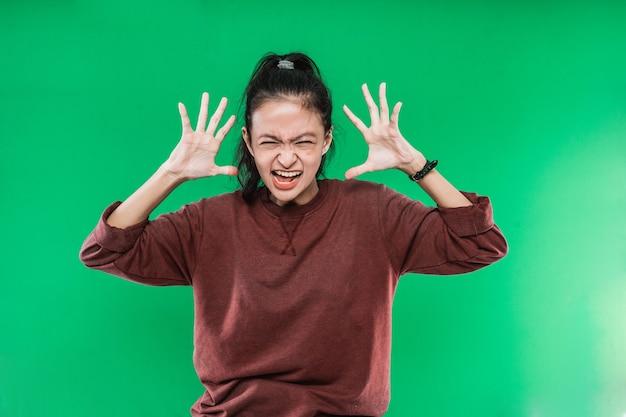 Mulher jovem gritando em pânico ou raiva, chocada, apavorada ou furiosa, com as mãos perto da cabeça contra um fundo verde