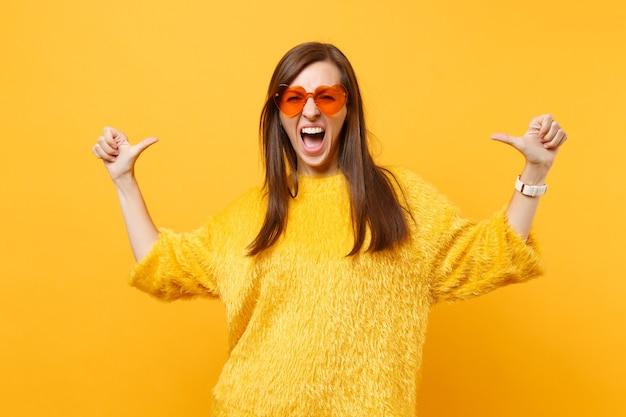 Mulher jovem gritando louca em suéter, calça branca, óculos coração laranja, apontando os polegares em si mesma isolada em fundo amarelo brilhante. emoções sinceras de pessoas, conceito de estilo de vida. área de publicidade.