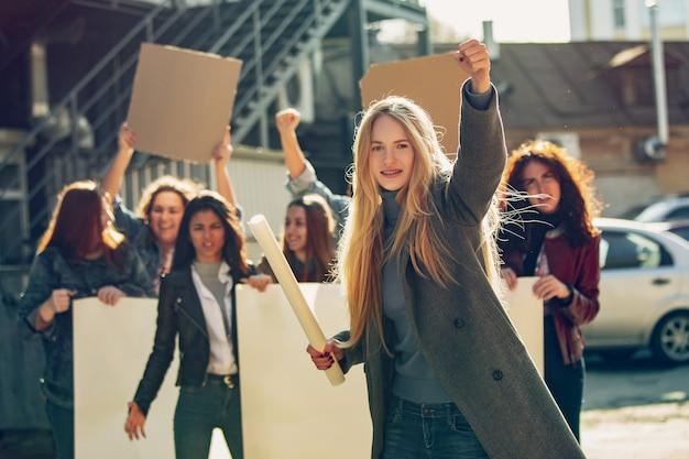 Mulher jovem gritando na frente de pessoas que protestavam sobre os direitos das mulheres e a igualdade nas ruas. reunião sobre problemas no local de trabalho, pressão masculina, violência doméstica, assédio. copyspace.