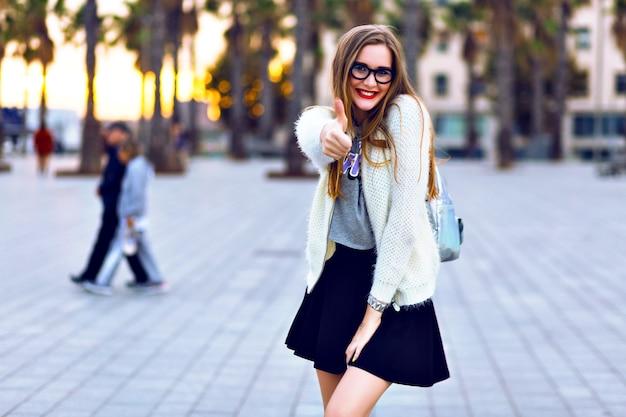 Mulher jovem hippie andando no entardecer, posando ao pôr do sol na cidade da califórnia, cores brilhantes. tempo quente de outono, roupa elegante da moda hipster maquiagem e óculos de sol.