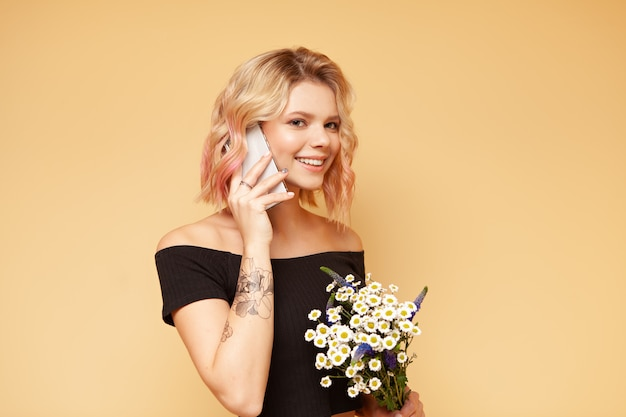 Mulher jovem hippie com cabelos encaracolados coloridos e tatuagem sorrindo e falando ao telefone, segurando flores