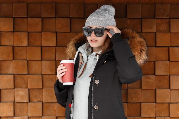 Mulher jovem hippie com chapéu de malha vintage em óculos de sol em uma jaqueta preta de inverno com um capuz de pele em uma camiseta da moda com uma xícara de café quente posa perto de uma parede de madeira ao ar livre. garota americana
