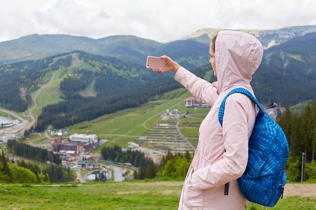 Mulher jovem hippie com mochila brilhante e jaqueta rosa com capuz em pé no topo da montanha, tirando foto, gravando novo vídeo para o blog de viagens