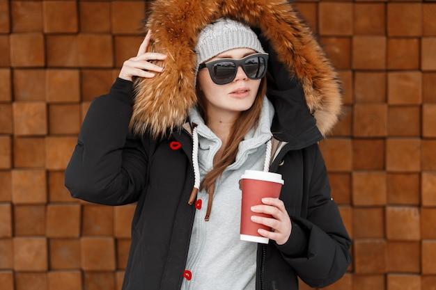 Mulher jovem hippie com um chapéu cinza de malha com uma elegante jaqueta de inverno com peles em um moletom azul quente, segurando uma xícara de café perto da parede de madeira. roupas de inverno
