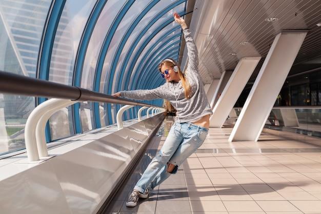 Mulher jovem hippie dançando se divertindo em um edifício urbano moderno, vestida com roupa casual, ouvindo música em fones de ouvido, vestindo jeans, suéter e óculos escuros
