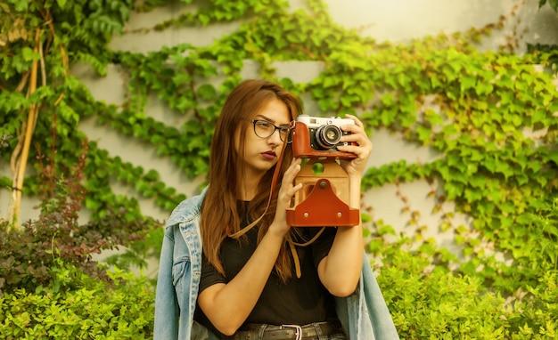 Mulher jovem hippie de jaqueta jeans e óculos curtindo a câmera retro de filme ao ar livre