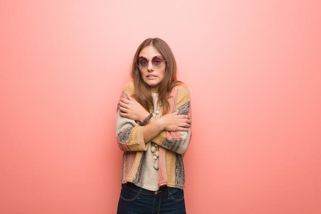 Mulher jovem hippie em fundo rosa, esfriando devido à baixa temperatura