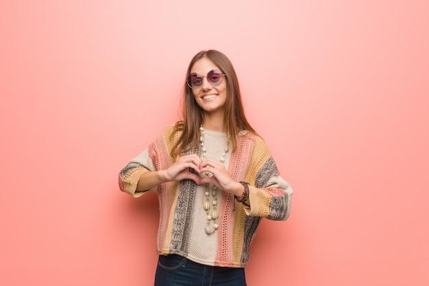 Mulher jovem hippie em fundo rosa, fazendo uma forma de coração com as mãos