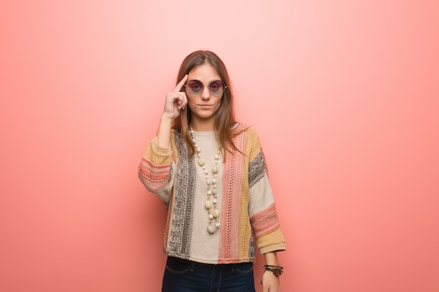 Mulher jovem hippie em fundo rosa, pensando em uma idéia