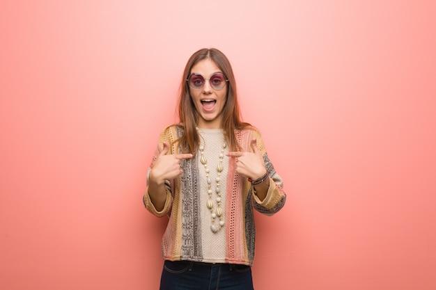 Mulher jovem hippie em fundo rosa surpreendeu, sente-se bem sucedido e próspero