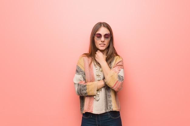 Mulher jovem hippie em fundo rosa tosse, doente devido a um vírus ou infecção