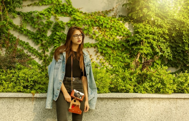Mulher jovem hippie em jaqueta jeans, óculos com câmera retro de filme ao ar livre