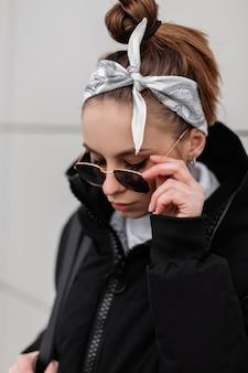 Mulher jovem hippie em óculos de sol da moda em uma elegante bandana com um casaco quente de inverno, posando em uma cidade perto de uma parede branca. garota da moda americana.