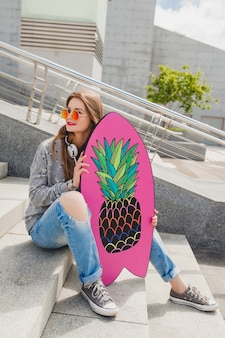 Mulher jovem hippie em óculos de sol rosa na rua com prancha de equilíbrio vestindo blusa e jeans