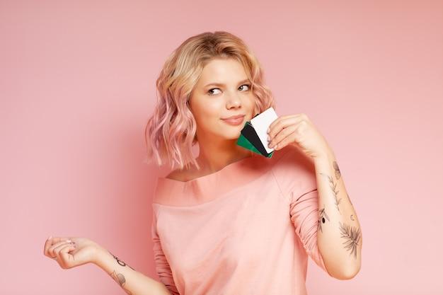 Mulher jovem hippie estudante com cabelos coloridos e tatuagem segurando os cartões de crédito