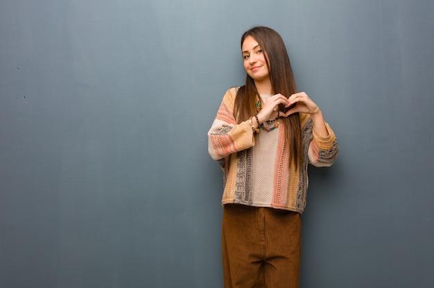 Mulher jovem hippie fazendo uma forma de coração com as mãos