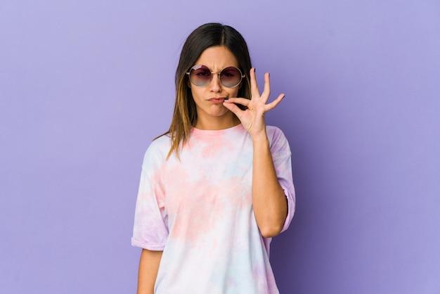 Mulher jovem hippie isolada em roxo com os dedos nos lábios, mantendo um segredo.