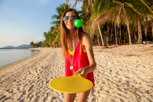 Mulher jovem hippie jogando pingue-pongue na praia tropical, férias de verão.