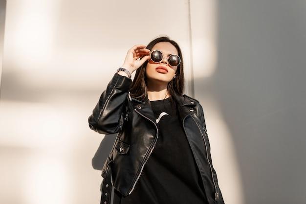 Mulher jovem hippie na moda em roupas da moda pretas com uma jaqueta de couro elegante olha através dos óculos de sol para a luz do sol na cidade
