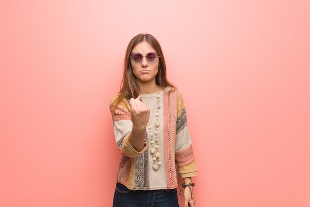Mulher jovem hippie na parede rosa, mostrando o punho para a frente, expressão de raiva