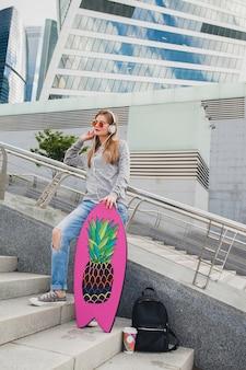 Mulher jovem hippie na rua com prancha de equilíbrio vestindo blusa e jeans