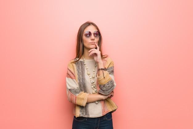Mulher jovem hippie no fundo rosa, duvidando e confuso