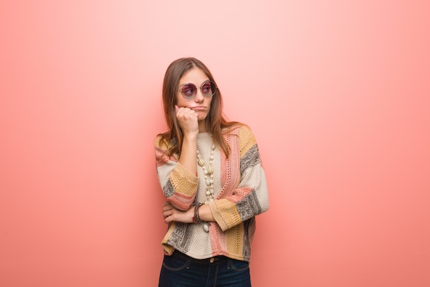 Mulher jovem hippie no fundo rosa pensando em algo, olhando para o lado