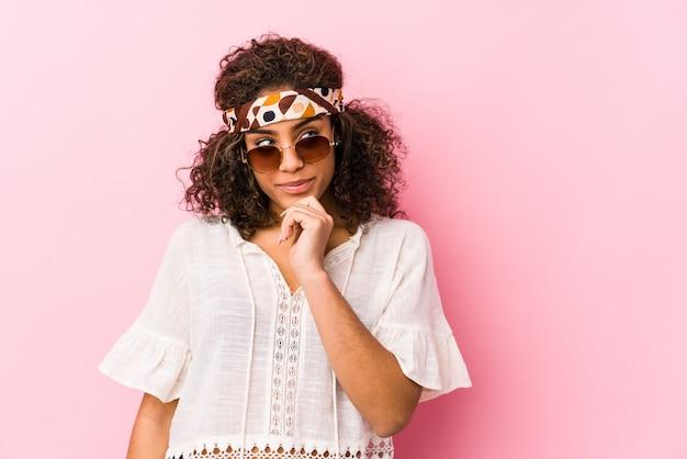 Mulher jovem hippie olhando de soslaio com expressão duvidosa e cética