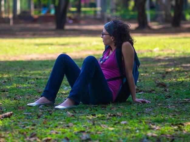 Mulher jovem hippie relaxando na grama no parque.