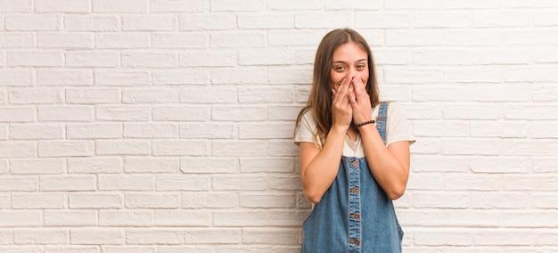Mulher jovem hippie rindo de alguma coisa, cobrindo a boca com as mãos