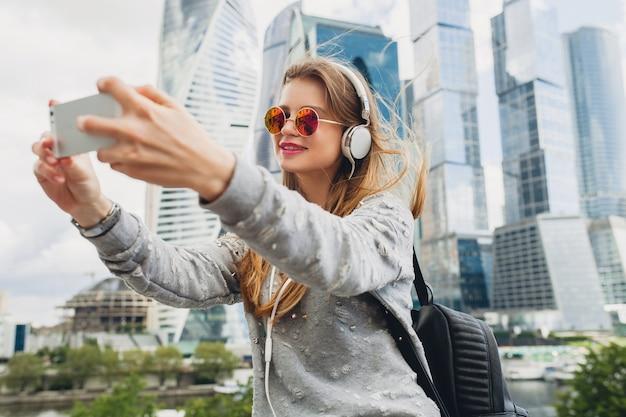 Mulher jovem hippie se divertindo na rua ouvindo música em fones de ouvido