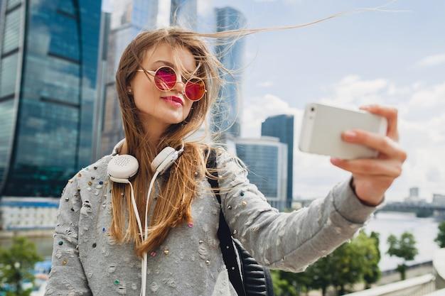 Mulher jovem hippie se divertindo na rua, usando óculos escuros cor de rosa