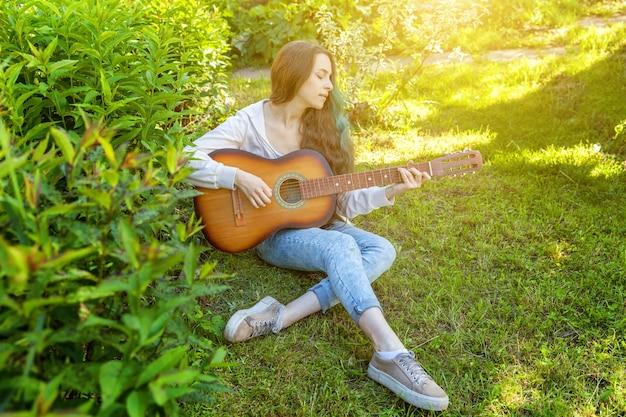 Mulher jovem hippie sentada na grama tocando guitarra no parque ou jardim
