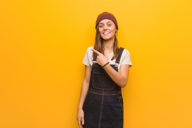 Mulher jovem hippie sorrindo e apontando para o lado