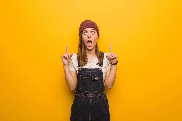 Mulher jovem hippie surpresa apontando para cima para mostrar algo
