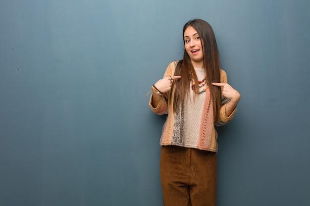 Mulher jovem hippie surpreso, sente-se bem sucedido e próspero