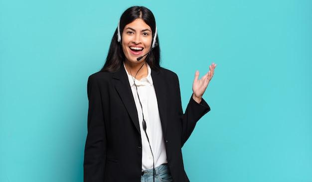 Mulher jovem hispânica de telemarketing sentindo-se feliz, surpresa e alegre, sorrindo com atitude positiva, percebendo uma solução ou ideia