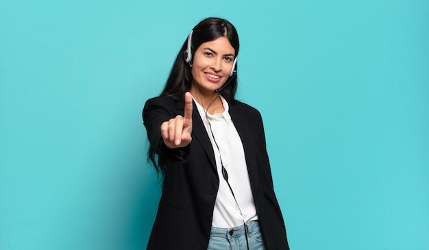 Mulher jovem hispânica de telemarketing sorrindo e parecendo amigável, mostrando o número um ou primeiro com a mão para a frente, em contagem regressiva